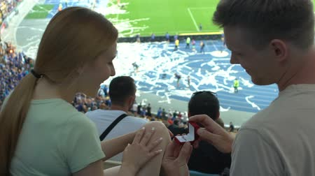 proposition : Boyfriend making proposal to girl during football match, romantic moment slow-mo