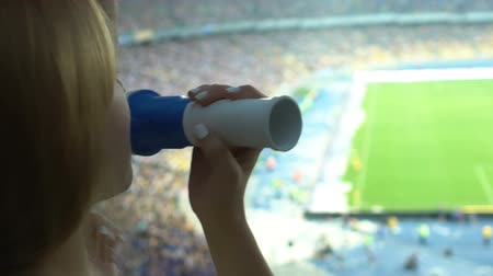 lelkesedés : Girl cheering football team with fan horn, celebrating scored goal, slow-motion Stock mozgókép