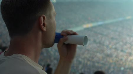 фэн : Male supporter blowing fan horn, excited with football game, celebrating goal Стоковые видеозаписи