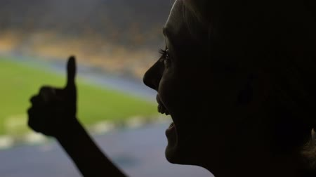 atributo : Happy woman fan cheering for football team winning on crowded stadium, thumbs-up Stock Footage