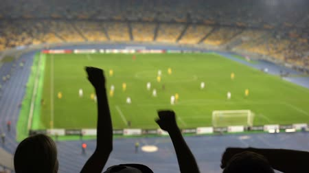 arquibancadas : Silhouettes of fans hands in stadium while watching football match, cheering