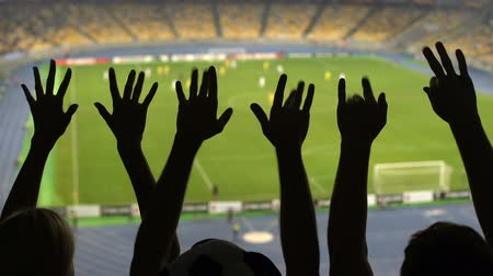 supportive : Silhouettes of soccer fans hands during match, crowded football stadium.