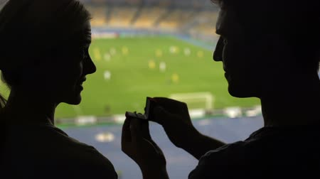 oświadczyny : Young man presenting his lady engagement ring during football match on stadium Wideo