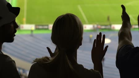 penas : Shadows of female and male football fans showing discontent with game at stadium