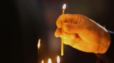 batismo : Devotee puts candle, praying for health, religious rituals in church, closeup