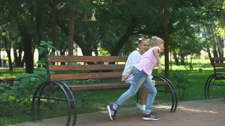 emeryt : Mature family couple watching children running and playing in park, generation Wideo