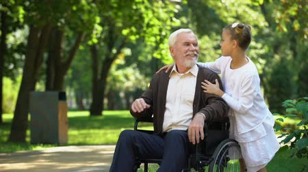 nursing : Little granddaughter helping disabled grandfather, love and care, family values Stock Footage