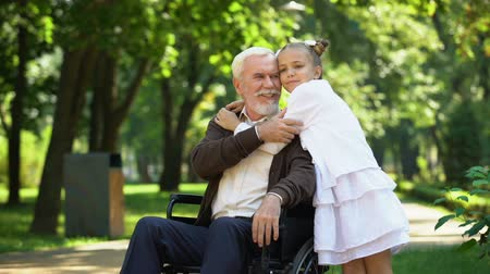 odpowiedzialność : Cute girl hugging grandfather sitting in wheelchair, walk in park, pastime Wideo