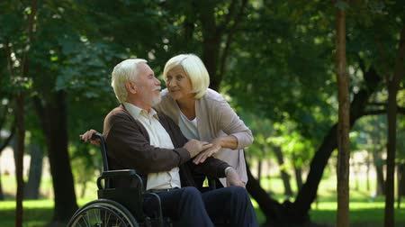 пенсионер : Mature couple resting in park looking at grandkids, man sitting in wheelchair Стоковые видеозаписи