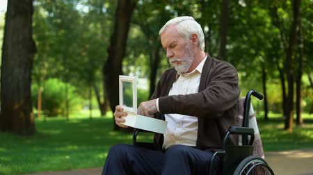 paraplegic : Disabled grandfather looking at military token in white box, homeland merits Stock Footage