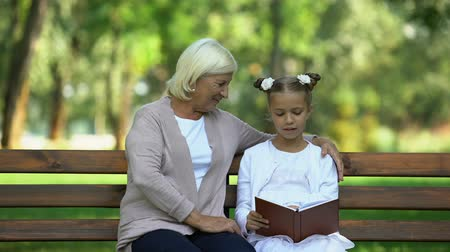 conta : Little granddaughter reading book aloud to her grandmother, pastime in park