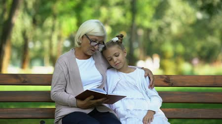 dziadkowie : Caring granny reading fairy tale to cute granddaughter sitting on bench in park