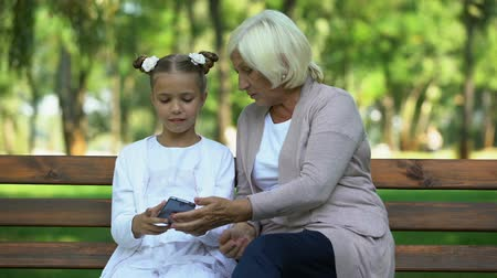 kloof : Cute granddaughter teaching granny how to use modern smartphone, generation gap