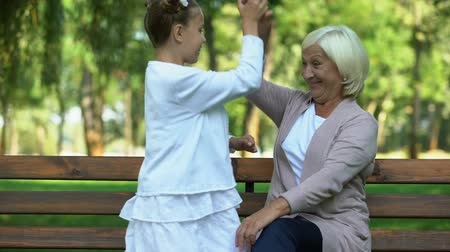 ailelerin : Granddaughter happily running to her grandmother and hugging, family values Stok Video