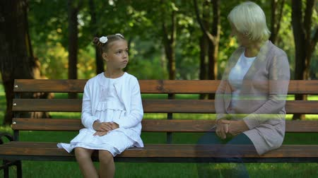 remembering : Girl remembering her grandmother, sitting on bench alone, loss of grandparent