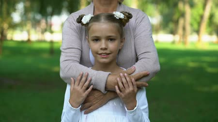 odpowiedzialność : Mature lady hugging little girl, social protection of children, family care