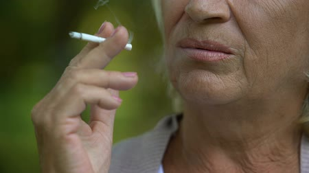zmarszczki : Female pensioner inhaling toxic cigarette smoke, bad habits, risk of lung cancer