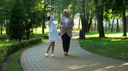 восхищенный : Happy granddaughter telling stories to grandmother, having fun together, gossips