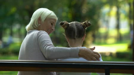 trusting : Granny hugging granddaughter, confidential conversation, trusting relations