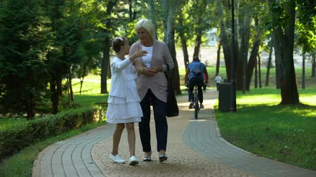 幼稚な : Happy girl telling stories to grandmother walking in park, trusting relations