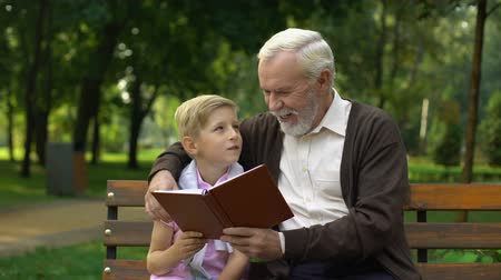unokája : Grandfather and grandson discussing book, spending time together, education