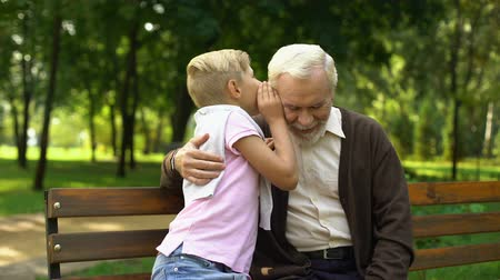 trusting : Grandson sharing secrets with grandfather, sitting in park, trusting relations