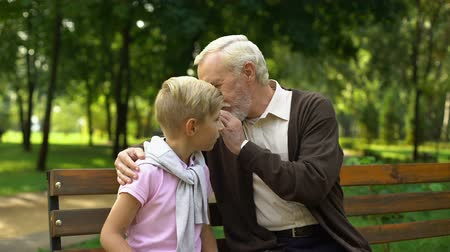 trusting : Grandfather telling secrets to kid, sharing life experience, tips for real men Stock Footage