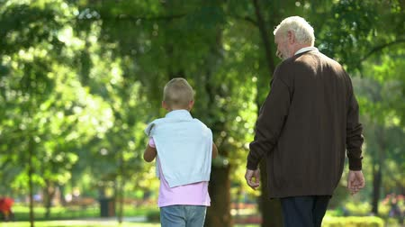 trusting : Granddad and grandson walking in park. Stock Footage