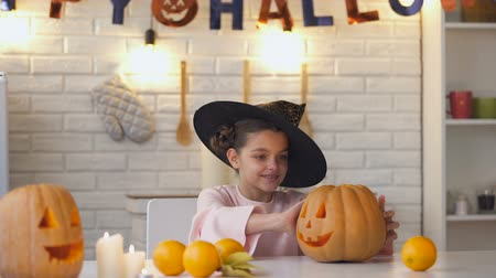 hallows : Cute little witch sitting at Halloween party with jack pumpkin showing thumbs-up