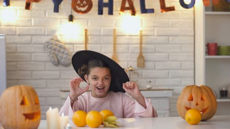 leaping : Little girl in scary witch costume jumping from under table, Halloween party