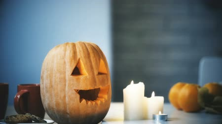 hallows : Creepy carved Halloween pumpkin smiling with flamed candles on table.