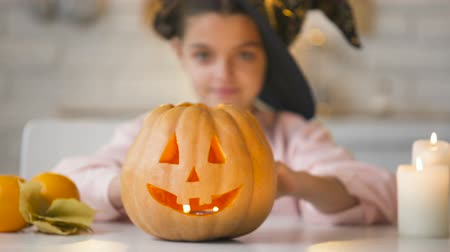 hallows : Little witch showing scary Jack-o-Lantern pumpkin, preparing for Halloween party Stock Footage