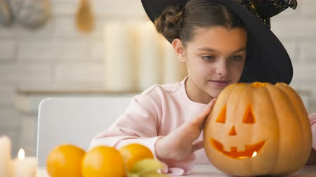 hallows : Cute girl in witch costume showing jack pumpkin and smiling, preparing for party