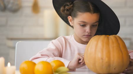 hallows : Pretty little girl making jack pumpkin and preparing for Halloween eve party