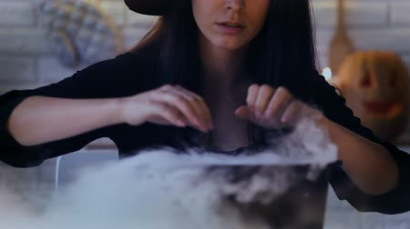 hallows : Scary witch making magic potions in her pot with white smoke, Halloween eve