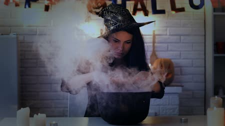 hallows : Mysterious young woman in witch costume cooking potion, preparing for Halloween