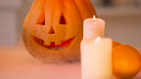 hallows : Smiling carved Halloween pumpkin with scary face illuminated by burning candles Stock Footage