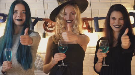 toverdrank : Three beautiful women showing thumbs up gesture, having fun on Halloween eve