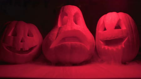 резной : Carved Jack Lantern pumpkins with smoke in red light darkness, Halloween party