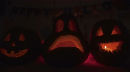 hallows : Spooky Halloween pumpkins with smoke and burning candles in red light darkness