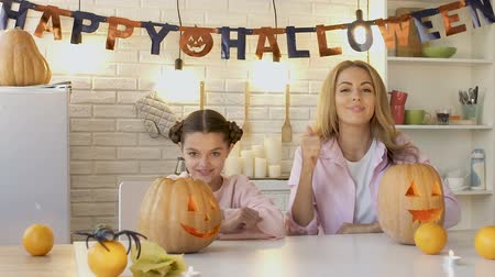 questão : Cheerful family showing thumbs-up into camera, satisfied with carved pumpkins