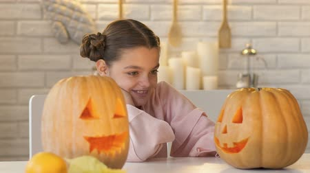 канун : Excited girl looking at jack-o-lantern, anticipation of funny fest of Halloween Стоковые видеозаписи
