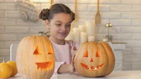 função : Girl looking at scary face of pumpkin, waiting evening to play trick-or-treating