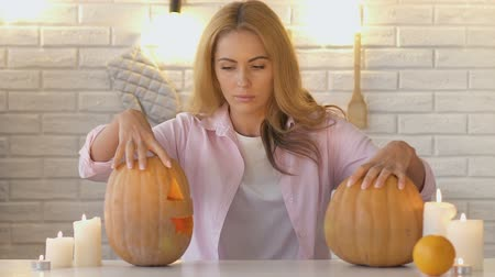 treating : Beautiful woman looking at pumpkins with candles inside and showing thumbs-up