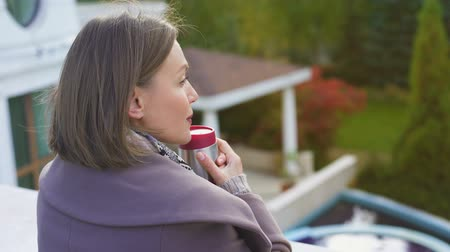 melankoli : Pensive woman with cup of coffee stands on balcony, warms up on cold autumn day