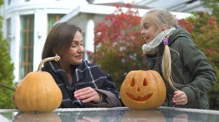 salva : Girl brings pumpkin jack-o-lantern to mother in yard, preparation for Halloween