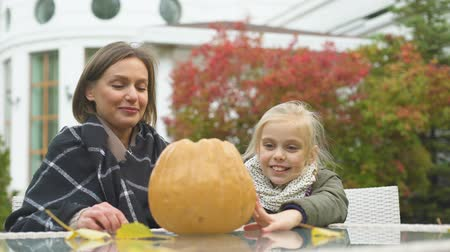 salva : Mother helping daughter to carve pumpkin Jack for Halloween school competition