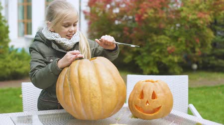 zvedák : Cute emotional girl carves pumpkin jack-o-lantern excited with process Halloween Dostupné videozáznamy