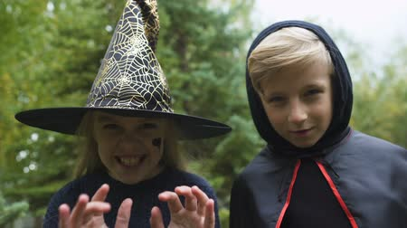 costumes : Girl in witch hat and boy in mantle chasing camera, growling spooky, Halloween