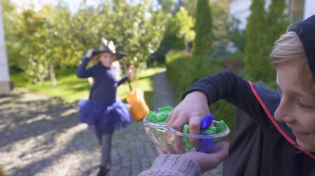 вкусности : Children take candy and run away, trick-or-treating on Halloween.